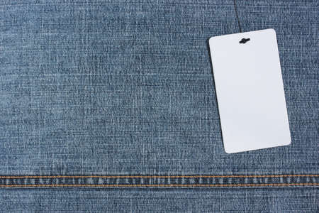 white empty label on a rope on blue denim, top view. mockup, scene creator. copy space.