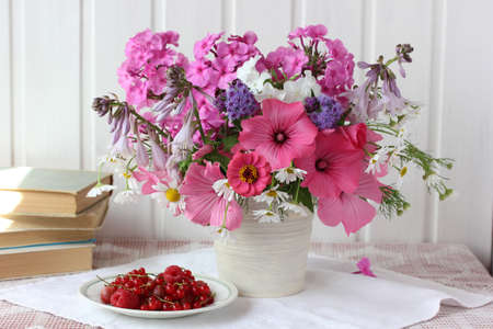 pink garden flowers, raspberries and currants on the table on a light background. Phlox, daisies and hollyhocks. still life with a bouquet and berries.