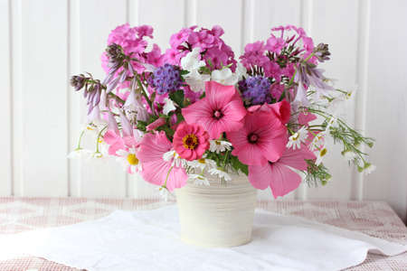 pink garden flowers on the table on a light background. Phlox, daisies and hollyhocks. still life with a bouquet.