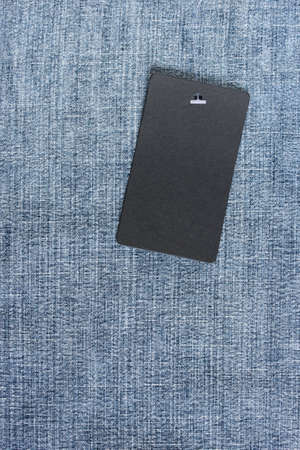 black empty label on a rope on blue denim, top view. mockup, scene creator. copy space.