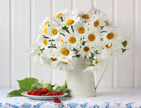 still life with daisies and berries. bouquet of garden flowers in a jug, raspberries and currants on the table.
