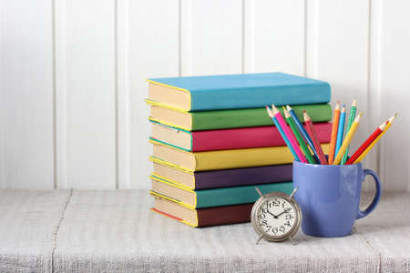 stack of books, colored pencils, and an alarm clock on the table. back to school, knowledge day. textbooks in color covers.