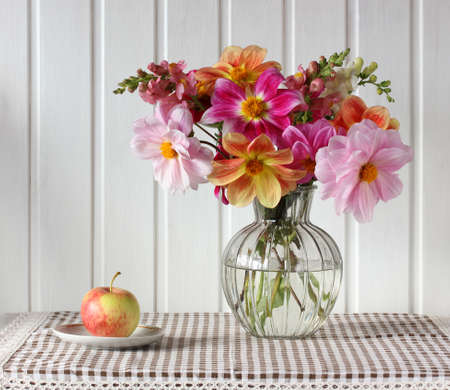 bouquet of dahlias and Apple, light still life. garden flowers in a glass vase. Stock Photo