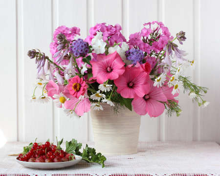 light summer still life with a bouquet. garden flowers and berries.
