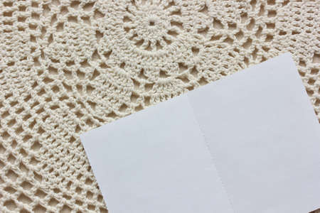 mockup, scene creator. white blank card on a lace tablecloth, top view.