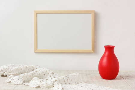 mockup, scene creator. empty frame on the wall, lace and red vase. selective focus. copy space.