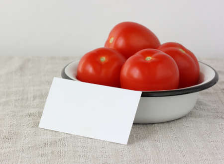mockup, scene creator. white empty card in a bowl with red tomatoes, selective focus. copy space. Stock Photo