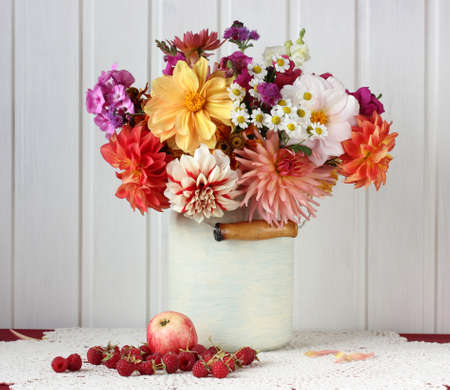 still life with a bouquet of garden dahlias, Apple and raspberry on a lace tablecloth. rustic interior. Stock Photo