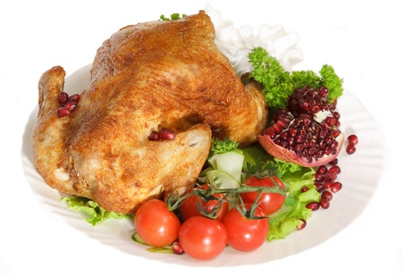 main: Roast chicken with tomatoes and a pomegranate Stock Photo