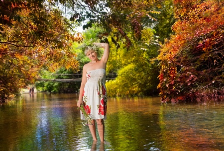 The girl with a bunch of flowers, standing in the river photo