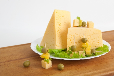 cheese with greens and olives on a wood board photo