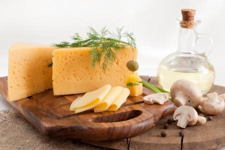 queso: queso con verduras y setas en un tablero de madera Foto de archivo