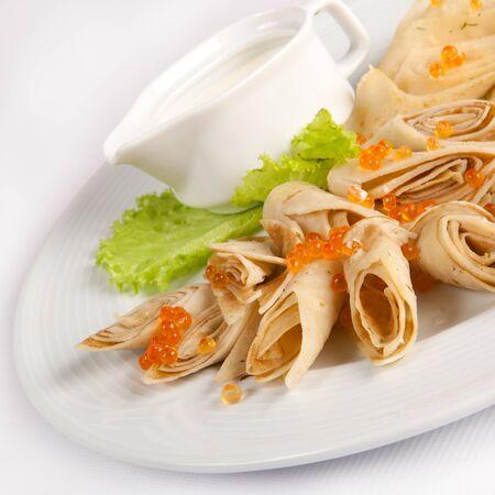 ensalada rusa: crepes con caviar rojo en un plato