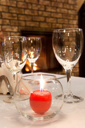 burning candle on the served table against a fireplace photo