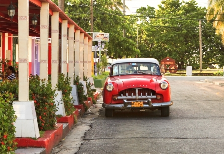 HAVANA, CUBA-MAY 14: Street scene with an old rusty american car on May 14, 2013 in Havana.These classic vintage cars that can be seen all over the country have become a worldwide known symbol of Cuba  Stock Photo - 21716127