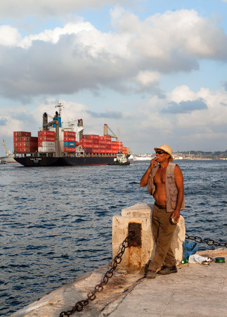 seawall: HAVANA, CUBA - MAY 19: Unknown Cuban fisherman catches a fish at the Malecon seawall in Havana. Fishing in the city helps to replenish the meager diet of poor people in Havana