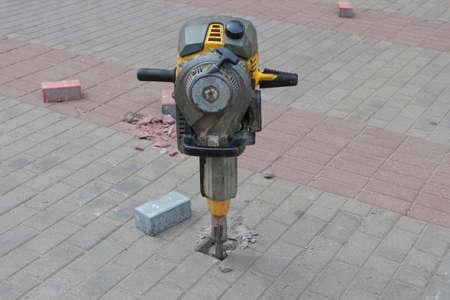 rupture: Jackhammer and pavement tiles.
