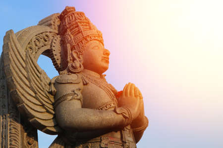 The bearer of Lord Vishnu, Garuda stands with folded hands in the sunlight. Stone statue of the Man-bird Garuda - servant of God.