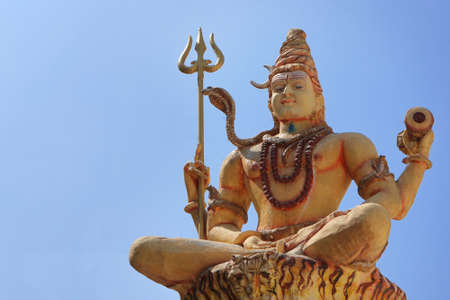 Shiva with a trident and a drum against the blue sky. Stock Photo