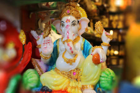 Figurine of God Ganesha. Indian souvenir. Beautiful Ganapati with four arms blesses with a gesture. Stock Photo