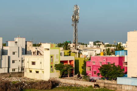 Chennai, Tamil Nadu, India - January 2020: A telecommunications tower rises above a low rise suburban neighbourhood in the city.