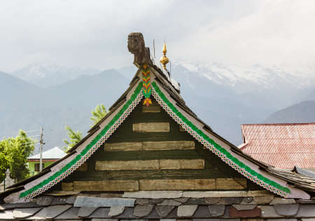 A wood and stone slanted slate roof and gable of an ancient Hindu temple in the Himalayan village of Kalpa in Kinnaur, India.