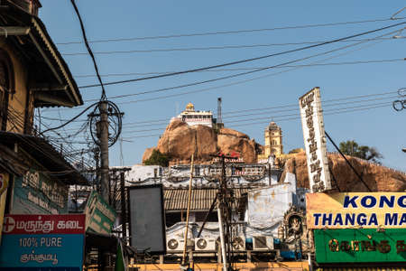 Trichy, Tamil Nadu, India - February 2020: The ancient Rock Fort temple on a rocky outcrop towering over a market in the city of Tiruchirappalli.