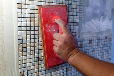 Réparations dans l'appartement: installation de la mosaïque sur le mur. Un ouvrier presse la mosaïque à l'aide d'un flotteur à coulis de caoutchouc.