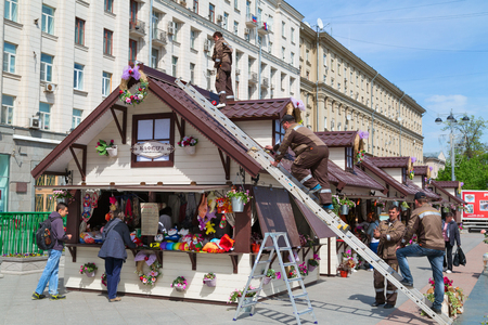 MOSCOW, RUSSIA - MAY, 8. The workers decorate a shopping kiosk for the annual spring market on Tverskaya square near the monument to Yuri Dolgorukiy on May 8, 2014. Moscow, Russia. Editorial