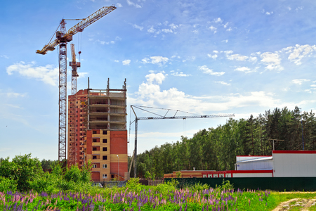 Construction of a new residential building among flower fields and close to forest. Moscow region, Russia