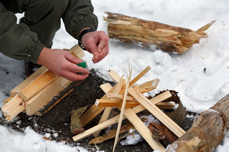 A man is going to strike a match to make a fire in the winter forest. Stock Photo