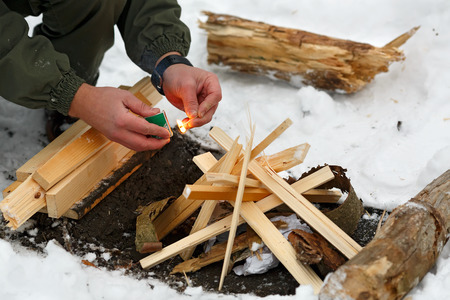 A man strikes a match to make a fire in the winter forest.