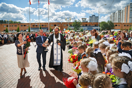 BALASHIKHA, RUSSIA - SEPTEMBER, 1. The priest sprinkles the crowd with holy water at the celebration of the beginning of the new school year on September 1, 2016 in Balashikha, Russia.