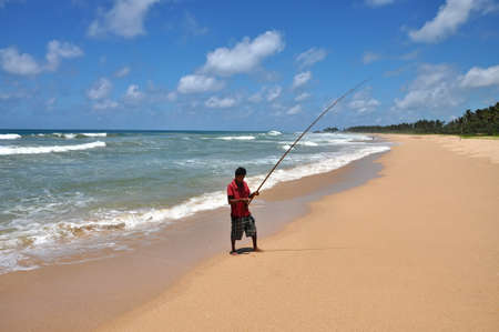 animal trap: A lone fisherman with a fishing rod on the beach. Sri Lanka.