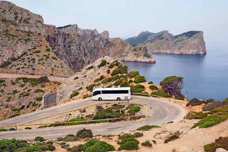 Tourist bus on the mountain road of the Cape Formentor as seen from the Formentor lighthouse. Island Majorca, Spain.