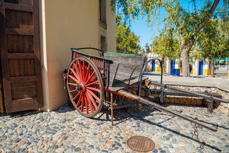 PORT AVENTURA SPAIN - MAY 11, 2015. Old wooden wagon with red wheels in the Far West area of theme park Port Aventura in city Salou, Spain.