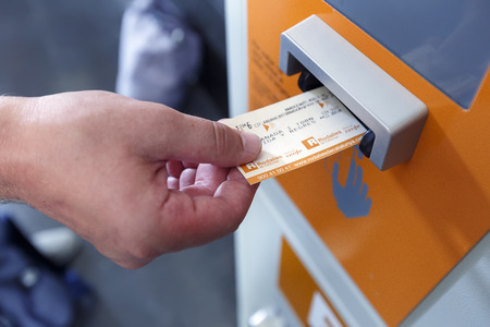 BARCELONA/ SPAIN - AUGUST 6, 2016: A man validating ticket in a punching machine for the train. Barcelona, Spain. 報道画像