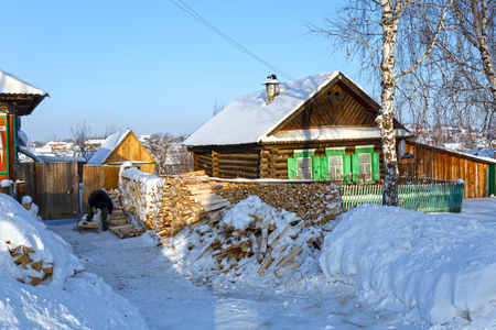 Snow-covered wooden houses and heaps of firewood in a russian old believer village Visim. Ural region, Russia. Stock Photo