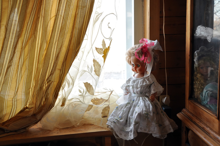 stool: Big doll in a smart white dress and with a bow in her hair on a wooden window sill. Russia Stock Photo