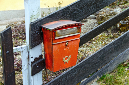 posthorn: Old red mailbox on a wooden fence. Austria. Editorial
