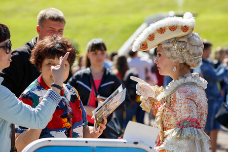 PETERHOF RUSSIA - JULY 2, 2017. Asian tourists want to be photographed with the model in an ancient court costume in the Peterhof park. Saint Petersburg, Russia. Editorial