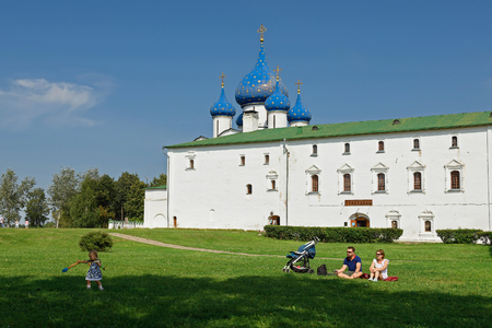 SUZDAL, RUSSIA - AUGUST 19, 2017. A young family with a small child sitting on the grass in front of the Cathedral of Nativity of Suzdal Kremlin . Suzdal, Russia.