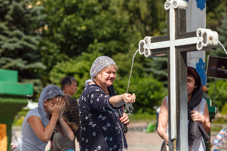 SERGIYEV POSAD RUSSIA - AUGUST 3, 2017. Christian women in traditional head scarfs near the Holy spring at the Sergiyev Posad monastery. Moscow region, Russia.