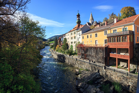View of the Mur river embankment in the fall. Historical town of Murau, Styria, Austria. Stock Photo