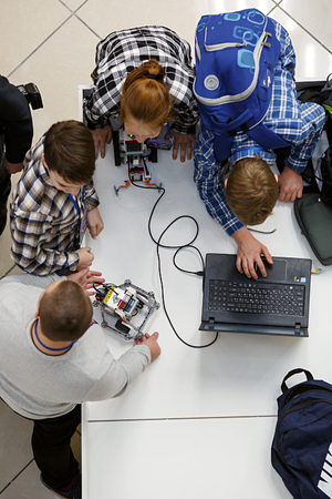 MOSCOW/ RUSSIA - DECEMBER 13, 2017. Group of children with laptop, programming the robot at robotics competitions.