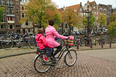 AMSTERDAM NETHERLANDS - OCTOBER 25, 2014. A brightly dressed woman on a bicycle, carrying her child on the rear child seat. Embankment of the Prinsengracht canal,   Amsterdam, the Netherlands.