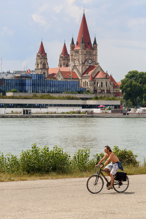 VIENNA AUSTRIA - JULY 9, 2017. A young man riding a bike on the Danube island, Donaustadt district. View of the Danube river and St. Francis of Assisi Church. Vienna, Austria.