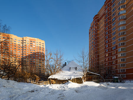 The old rickety wooden house in the courtyard of the new high-rise residential buildings. City of Balashikha, Moscow region, Russia. Stock Photo