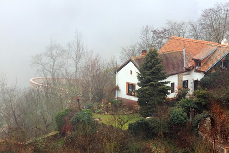 Small cozy house with a tile roof on the steep bank of the Thaya river, covered with fog. Znojmo, Czech Republic, Europe.