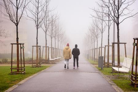 Two men walking along a foggy alley in the city park of Znojmo on a winter day. Znojmo, Czech Republic, Europe Foto de archivo